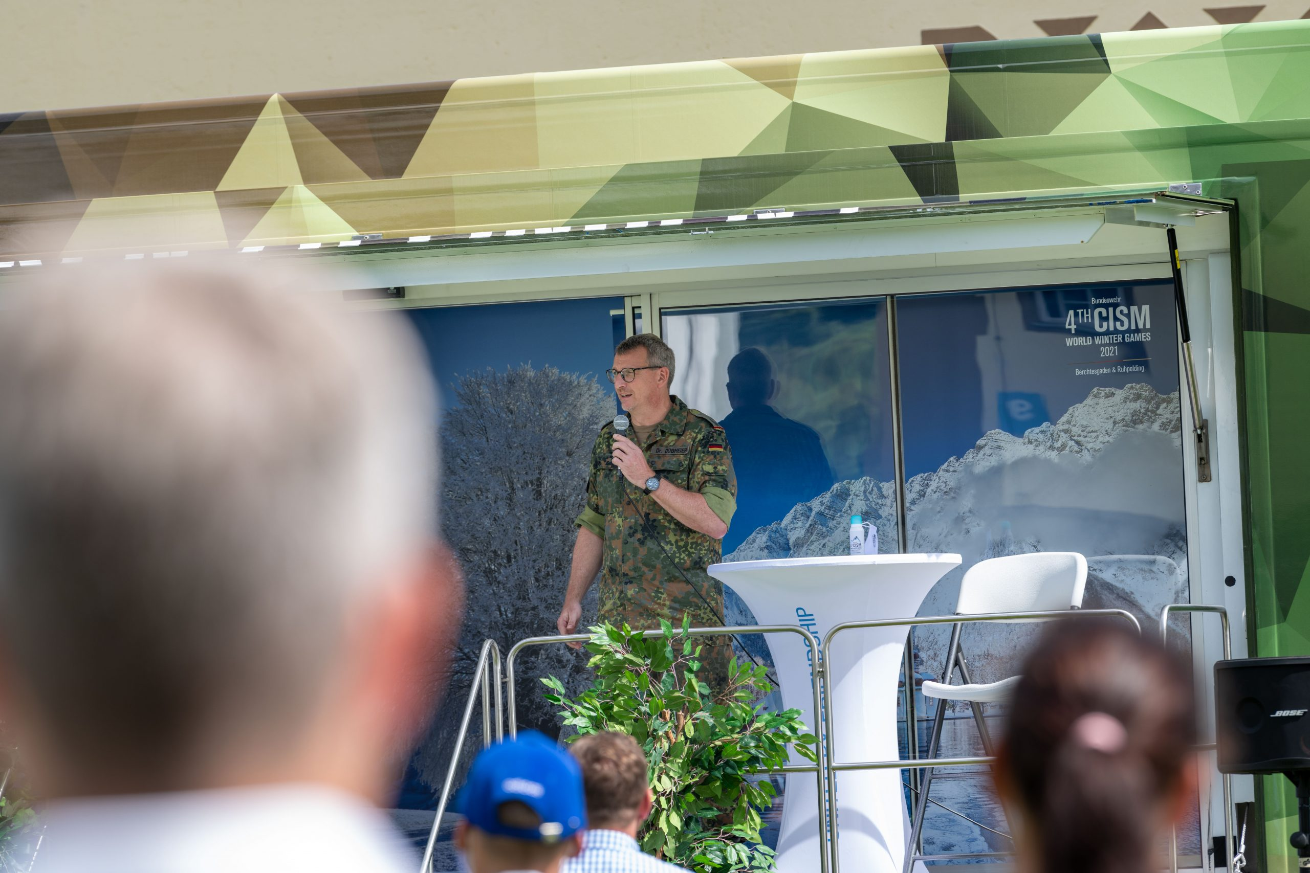 Lieutenant Colonel Dr. Dobmeier, the chief of the Organizing Staff, standing on the stage and speaking into a microphone